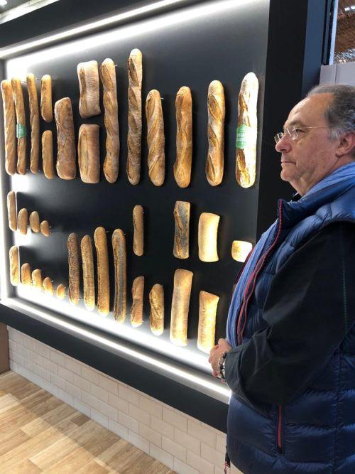 Don José R. Ferré, Presidente de Ferré & Consulting Group  observando un mural lleno de panes